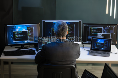 businessman looking at multiple computer screens