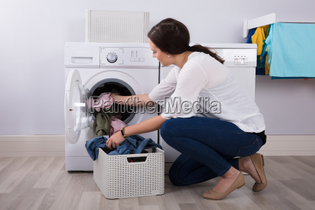 woman loading clothes in washing machine