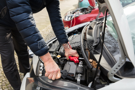 person using jumper cables to charge