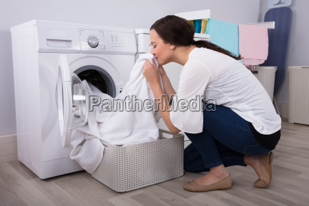 woman smelling cloth after washing in