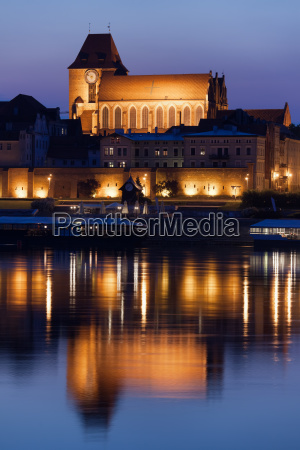 torun cathedral with reflection on vistula