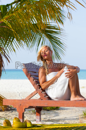 young blonde girl sunbathing on sunbeds