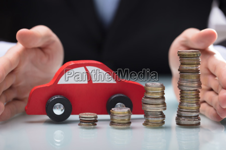 businessman protecting car and stacked of