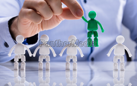 person selecting green figure amongst white