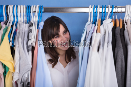 woman looking at variety of clothes