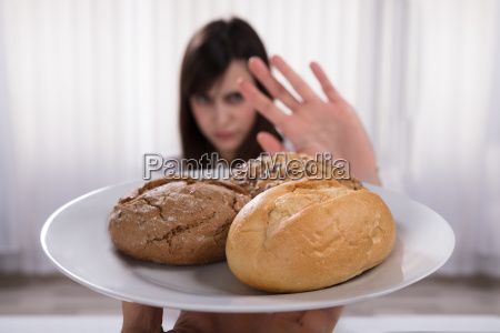 woman refusing plate of bread and
