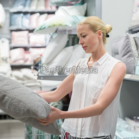 beautiful housewife buying white curtains in