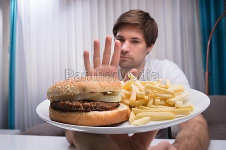 man refusing unhealthy food