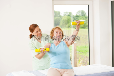 patient with physiotherapy with dumbbells in