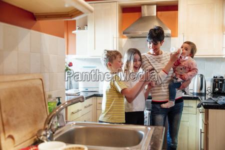 multitasking mum with her children at