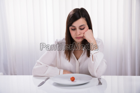 woman sitting with plate of cherry