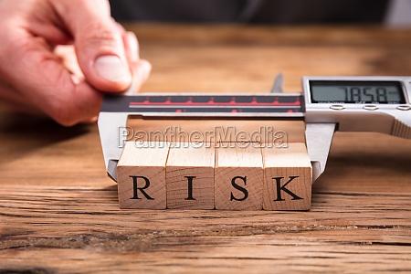 human hand measuring risk wooden blocks
