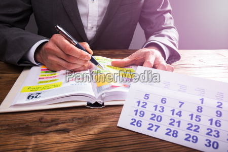 businesspersons hand checking schedule in diary