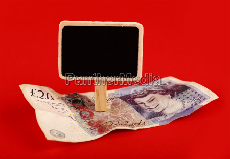 pound banknote and blackboard sign on