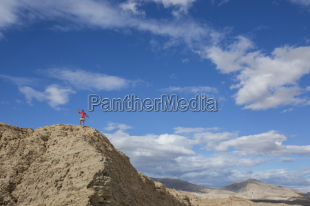 woman standing on top of hill