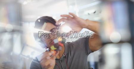 focused innovative male entrepreneur examining prototype