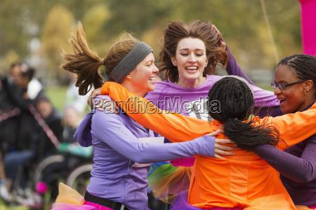enthusiastic female runners finishing charity run