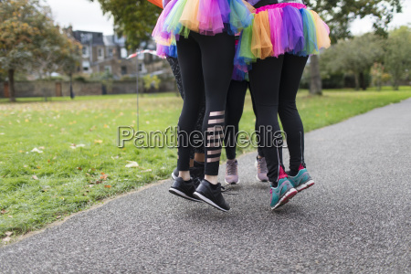enthusiastic female runners in tutus jumping
