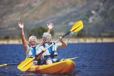 playful energetic active senior couple kayaking