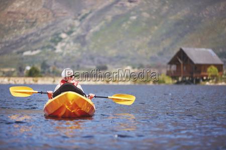 senior man kayaking on sunny summer