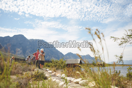 friends hiking on footpath along sunny