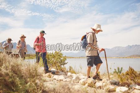 active senior friends hiking along sunny