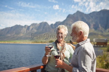 smiling active senior couple drinking red