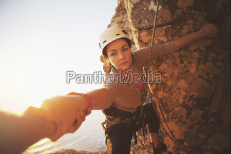 focused female rock climber reaching for