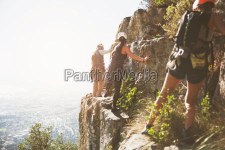 rock climbers climbing rocks above sunny