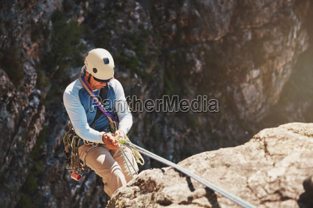 male rock climber rappelling descending from