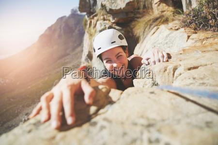portrait smiling confident rock climber reaching
