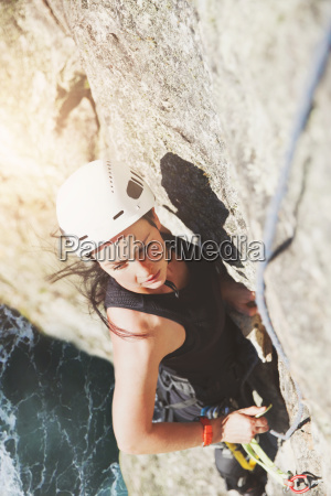 determined focused female rock climber scaling