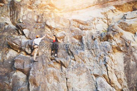 rock climbers high fiving on rock