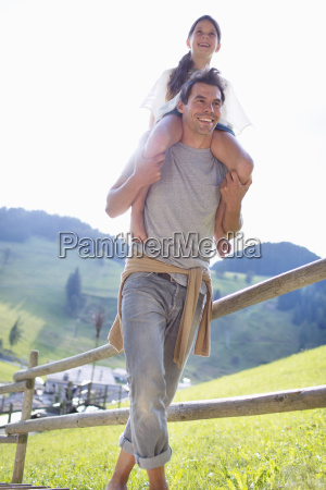 father carrying daughter on shoulders on