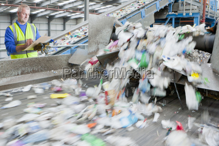 male worker with clipboard in waste
