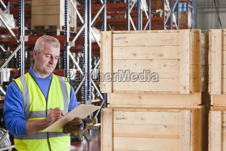 worker with clipboard in warehouse dispatch