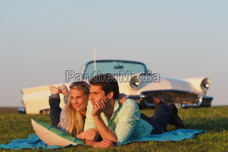 couple lying on blanket in countryside