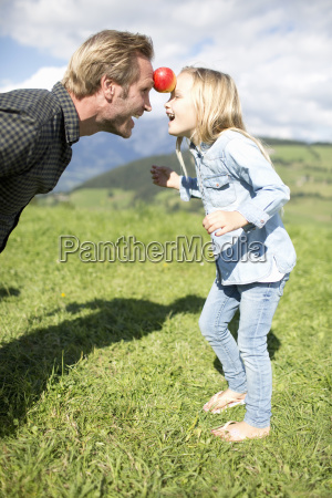father and daughter balancing an apple