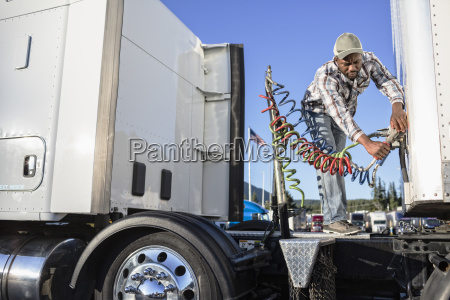 black man truck driver attaching power