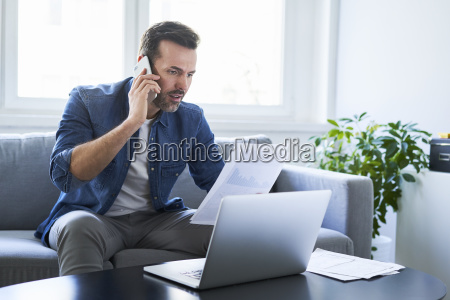 serious man with documents and laptop