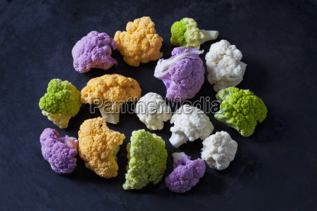 coloured cauliflower florets on dark background