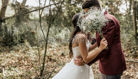 unrecognizable bride and groom kissing in