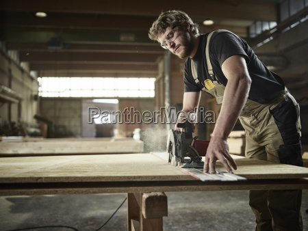 carpenter sawing wood with handsaw