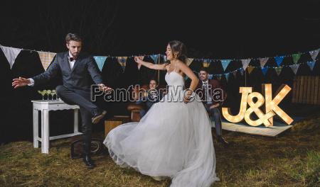 happy bride and man dancing on