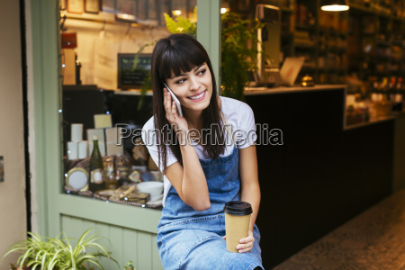 smiling woman sitting at entrance door