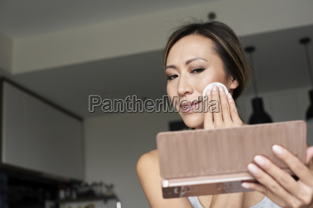 woman at home using hand mirror