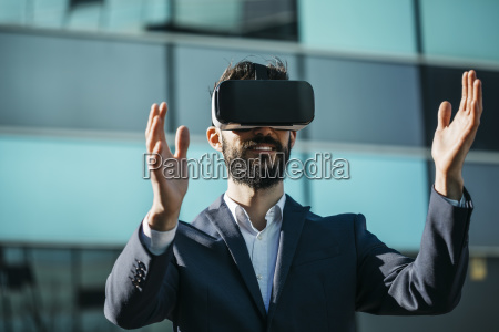 businessman using virtual reality glasses outside