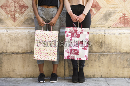 two women with shopping bags partial