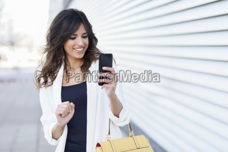 portrait of smiling businesswoman using cell