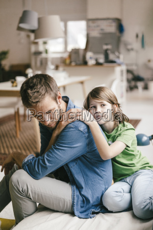 son consoling sad father at home